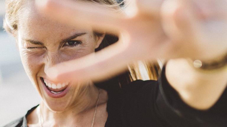 Eine Frau schaut lachend durch ihre V-Finger.