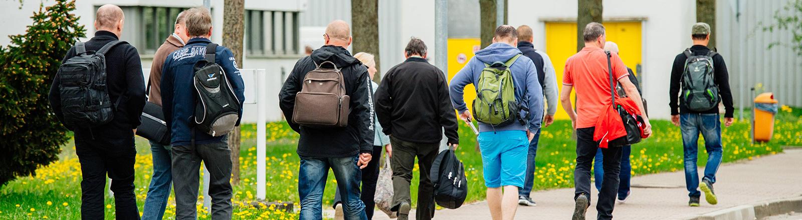 Männer mit Rucksäcken gehen eine Straße entlang.