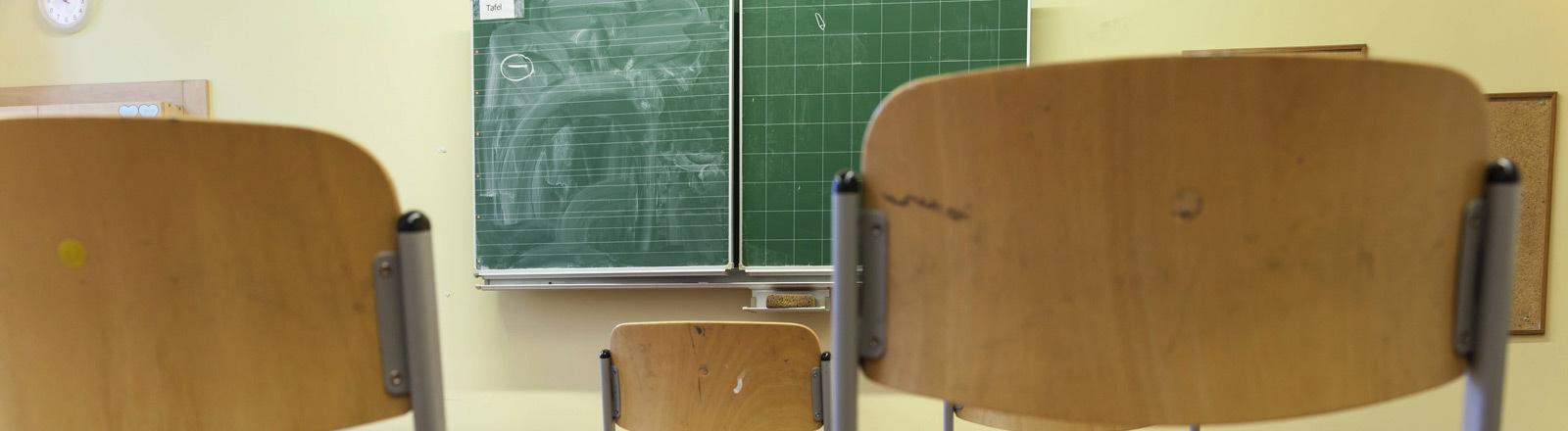 Ein leerer Schulraum mit hochgestellten Stühlen.