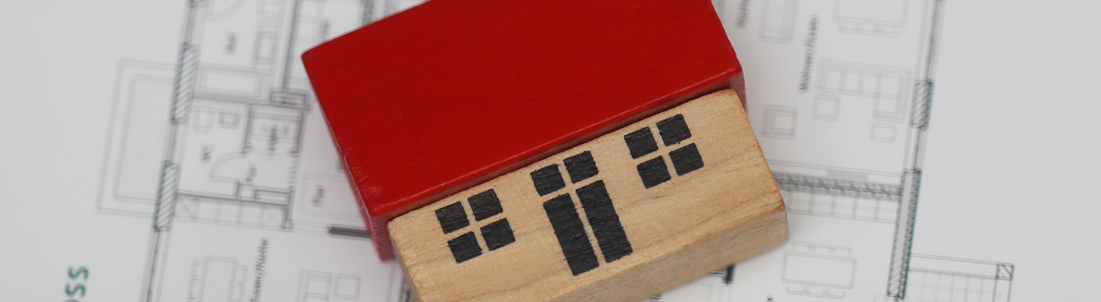 Ein Bauklotz in der Form eines Hauses liegt auf dem Grundriss einer Wohnung.