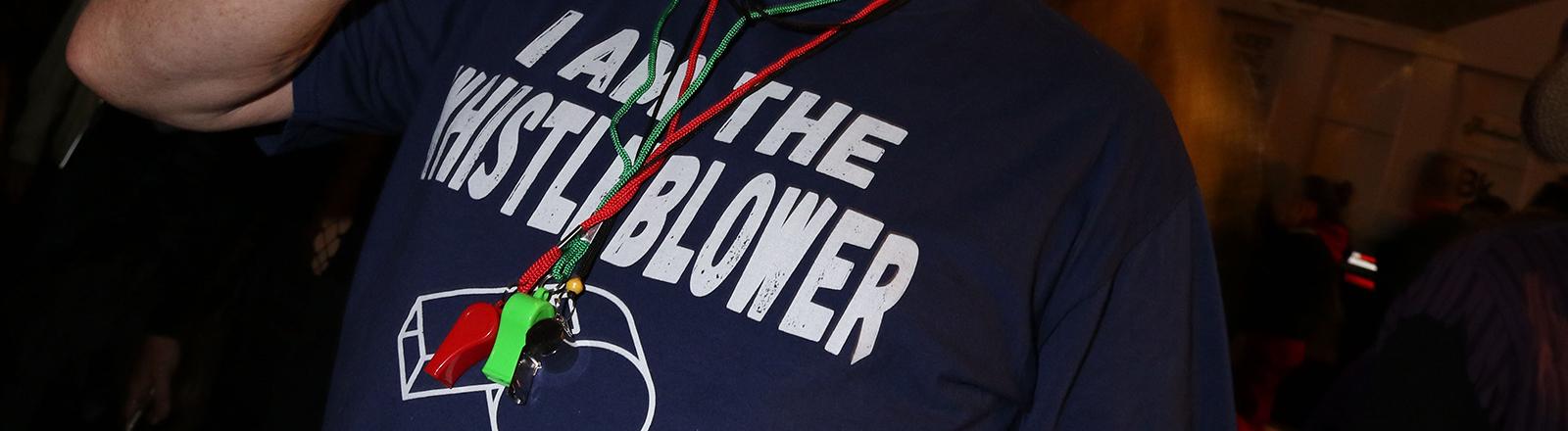 """Ein Mann mit einem T-Shirt auf dem steht """"I am the whistleblower""""."""