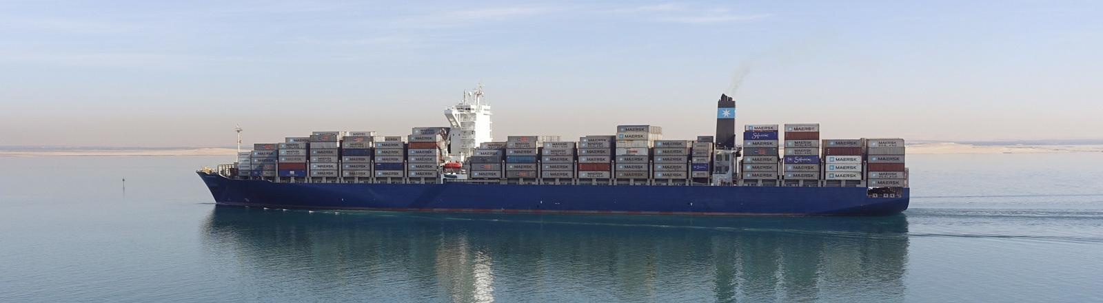Ein großes Containerschiff fährt sehr langsam auf dem Meer.