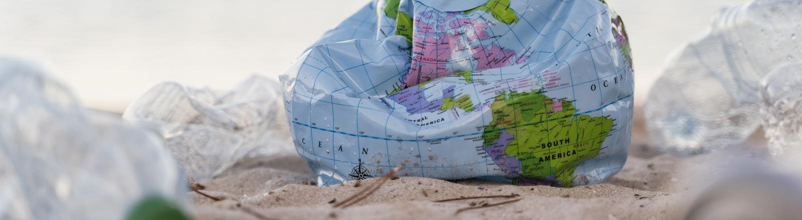 Weltkugel-Ball am Strand umringt von Plastikflaschen