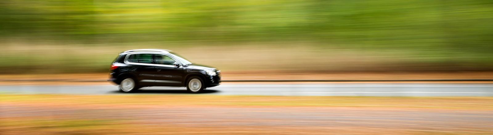 VW Tiguan (SUV) fährt schnell über eine Straße.