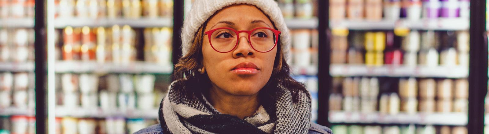 Eine Frau steht in einem Supermarkt und guckt skeptisch.