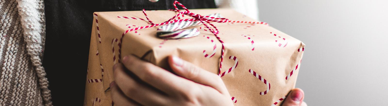 Frau hält Geschenk im Arm