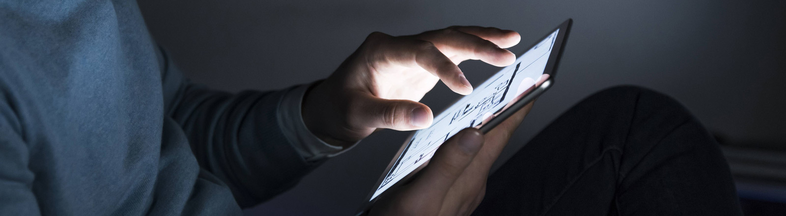 Ein Mann blickt auf sein Tablet.