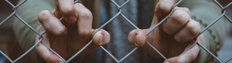 Hände am Zaun festhalten
