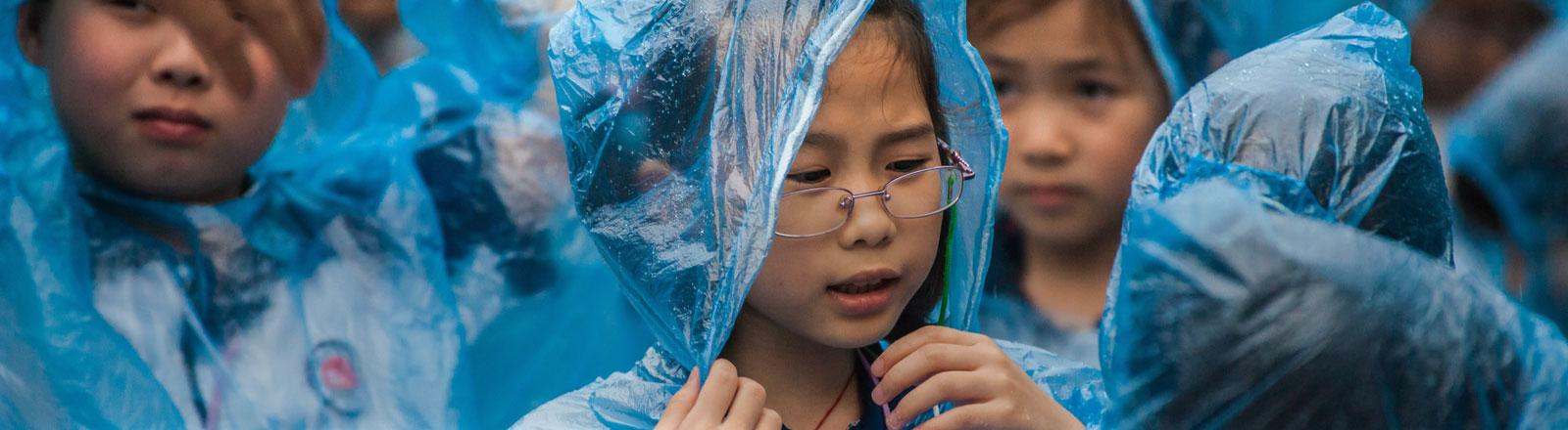 Chinesische Kinder im Regen.