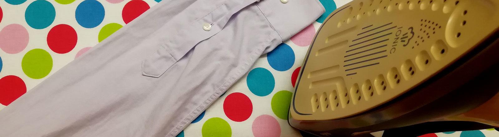 Bügelbrett mit einem Hemd und einem Bügeleisen darauf.