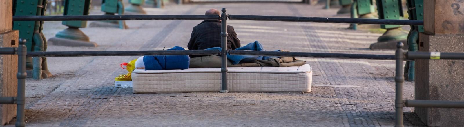 Obdachloser Mann sitzt auf einer Matratze unter dem Hochbahnviadukt in Berlin.