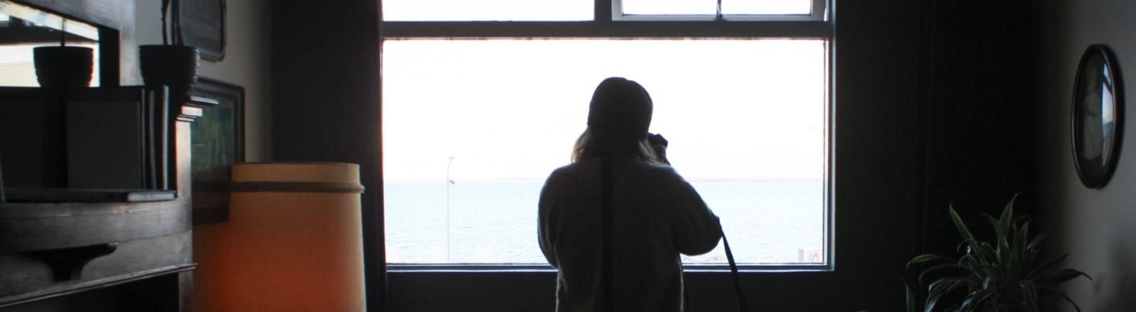Frau steht mit Rücken zum Beobachter am Fenster