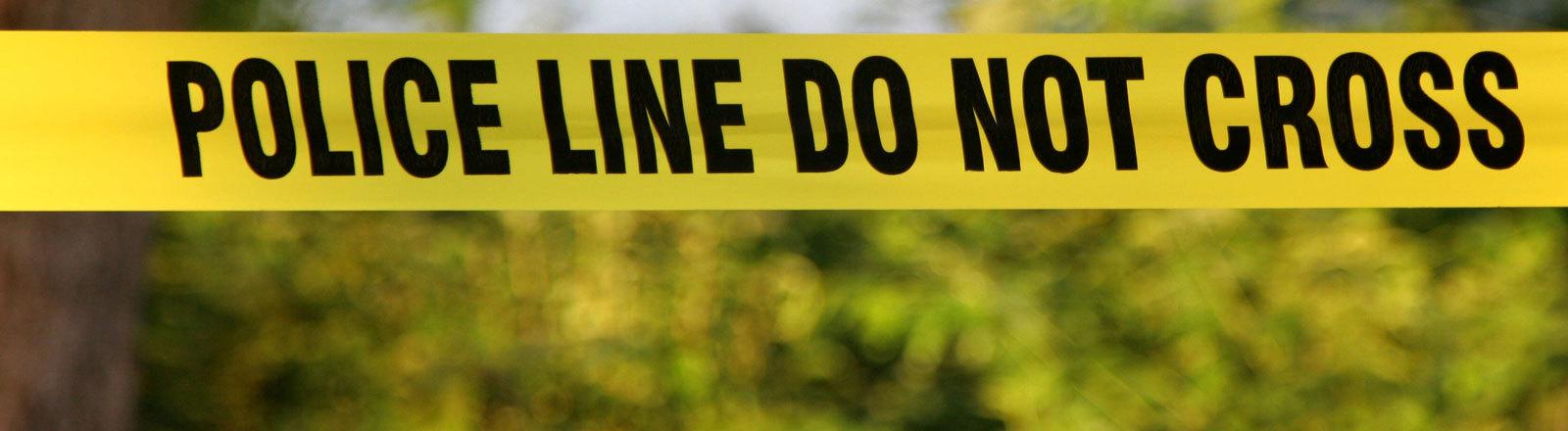 Polizeiabsperrung  an einem Tatort mit einem Flatterband.