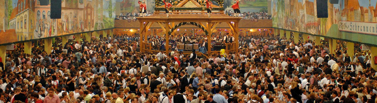 Menschen feiern beim Oktoberfest in einem Bierzelt.