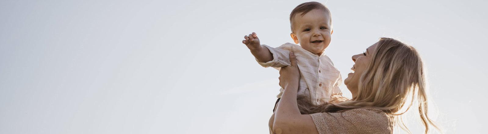 Eine Frau hält ihr Baby auf dem Arm.