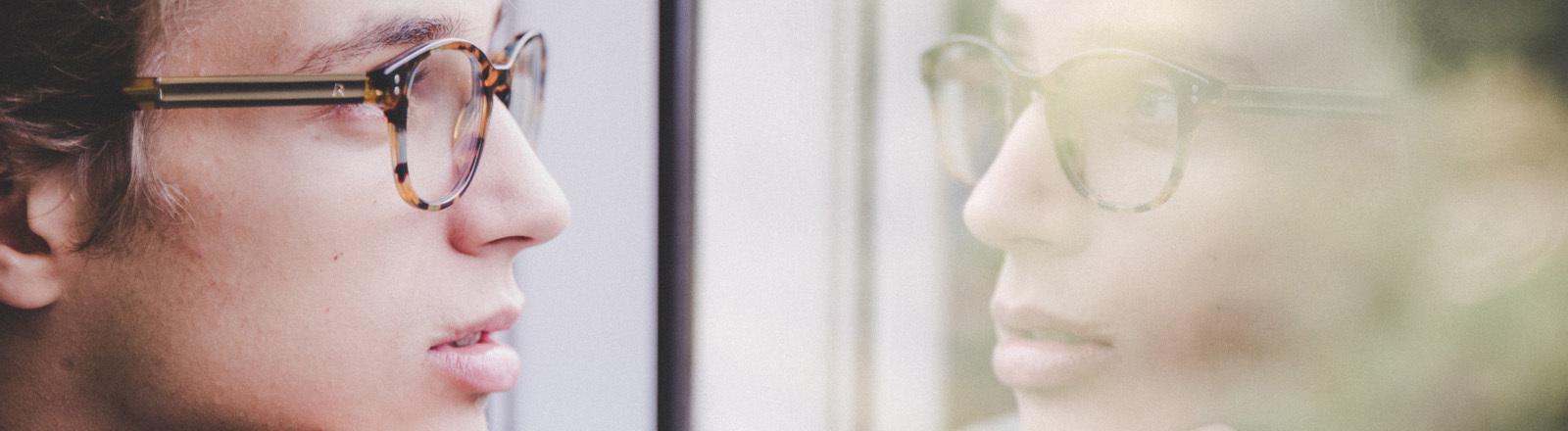 Junger Mann sieht im Fenster sein Spiegelbild