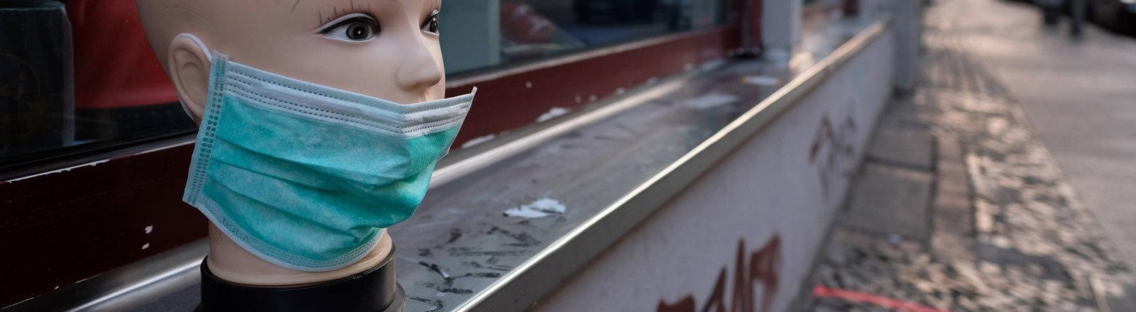 Vor einem Laden in der Oranienstraße in Berlin-Kreuzberg weist ein Puppenkopf mit einem Mundschutz auf den Verkauf von Atemschutzmasken hin.