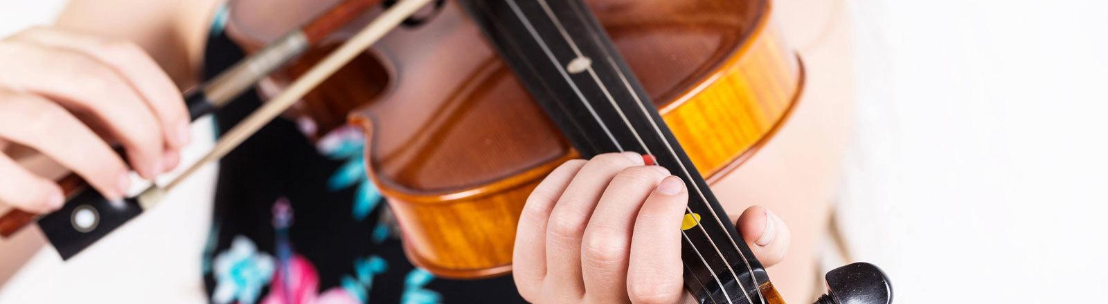 Ein junges Mädchen spielt Geige.