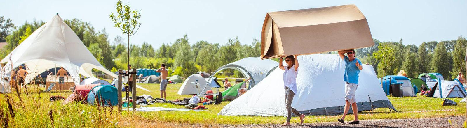 Ein Mann und eine Frau tragen ein Pappzelt - hinter ihnen sind auf einer Wiese konventionelle Zelte zu sehen.
