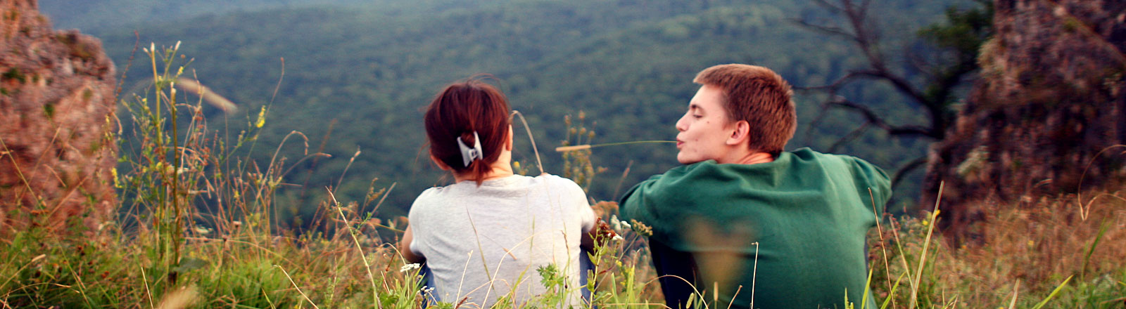 Ein Jugendlicher sitzt neben einem Mädchen und versucht Kontakt mit ihr aufzunehmen, er hat eine Getreideähre im Mund