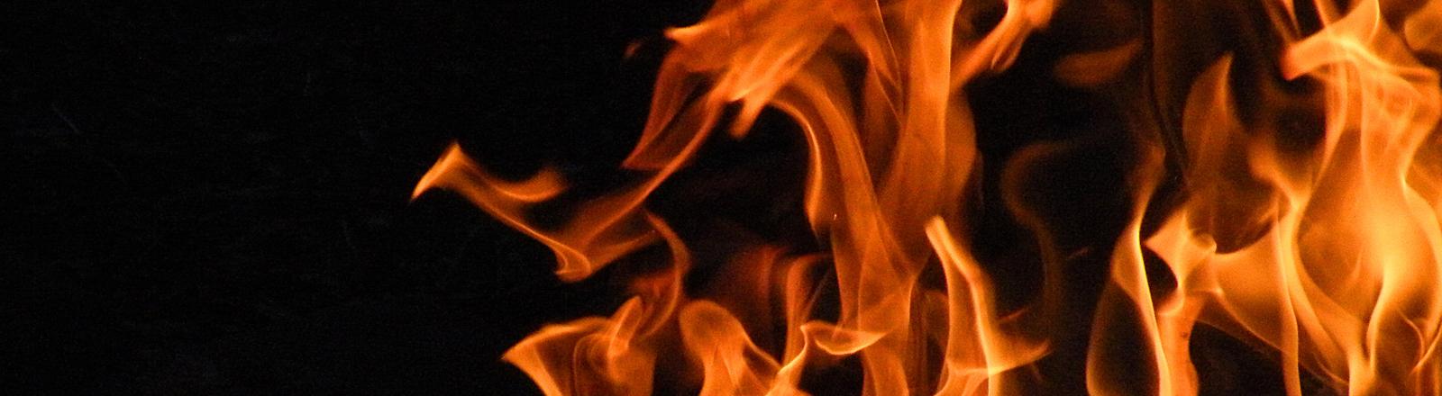 Flammen lodern in der Nacht.