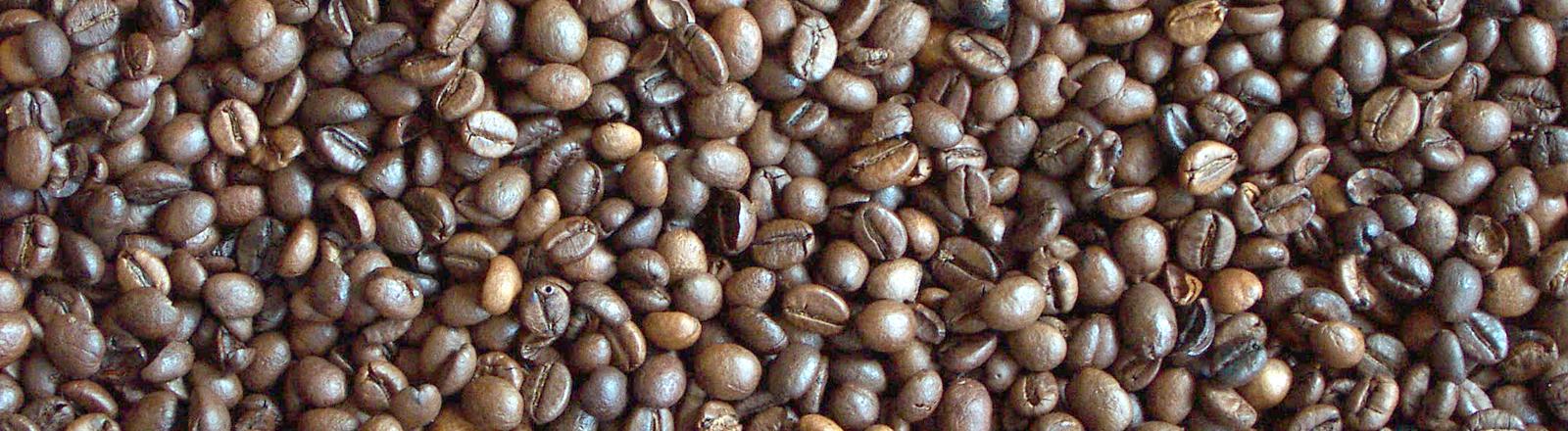 Kaffeebohnen liegen auf einem Tisch.