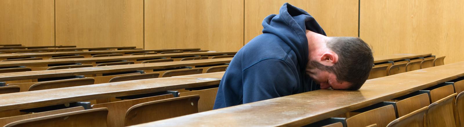 Ein junger Mann sitzt verzweifelt in einem Hörsaal.