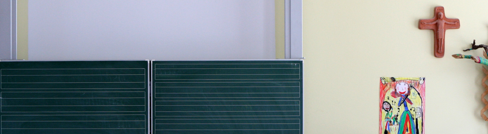 Eine Schulklasse, in der ein Kreuz an der Wand hängt.