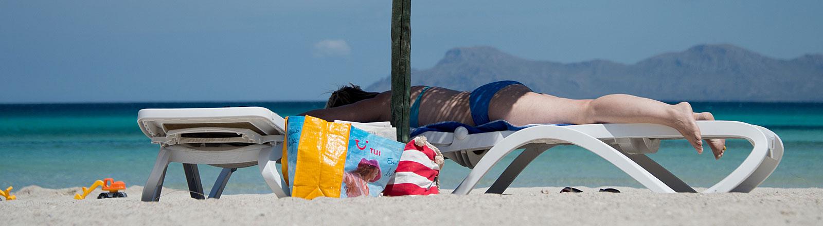 Eine deutsche Touristin liegt in Mallorca am Strand auf einer Liege, Bild: dpa