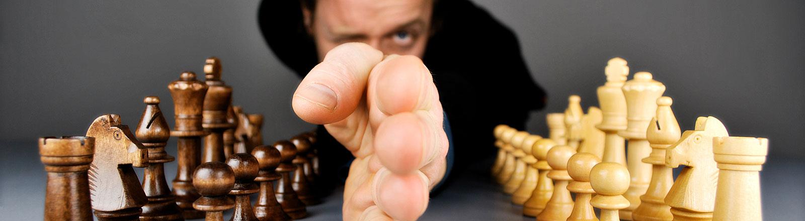 Ein Schiedsrichter hält seine Hand zwischen die beiden Figuren-Ensembles eines Schachbretts.