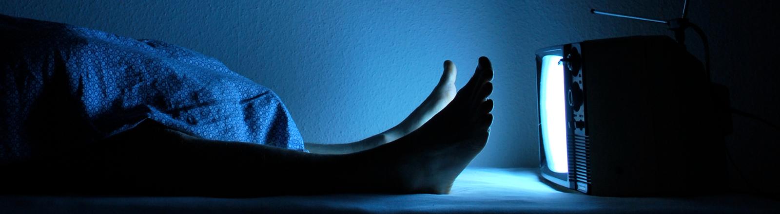 Nackte Füße vor dem Fernseher.