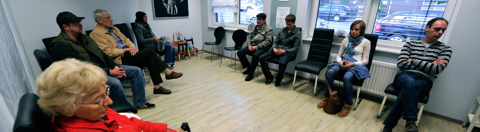 Acht Personen sitzen in einem Wartezimmer einer Praxis