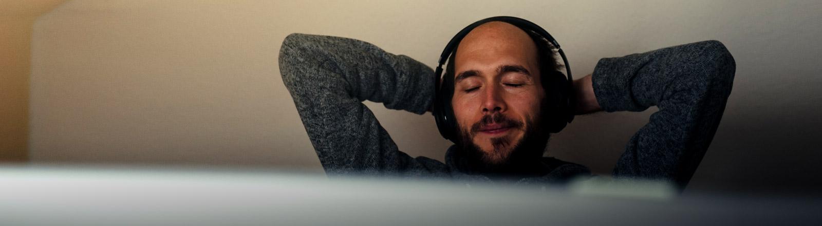 Ein Mann mit Kopfhörern verschränkt die Arme über dem Kopf.