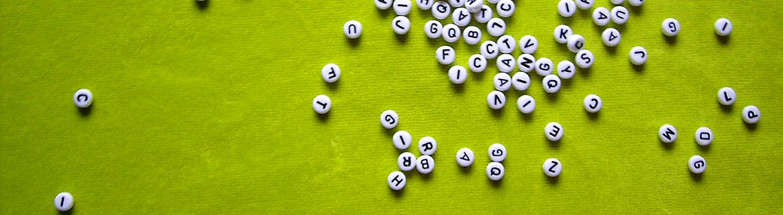 Unzählige Buchstaben auf grünem Grund.