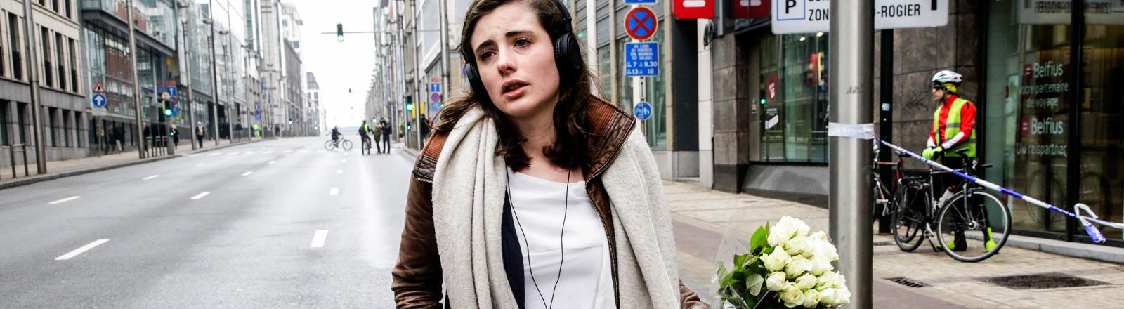 Eine junge Frau mit einem Blumenstrauß auf einer leeren Straße in der Nähe der Metro-Station Maelbeek, wo am 22.3. viele Menschen bei einem Terroranschlag starben.