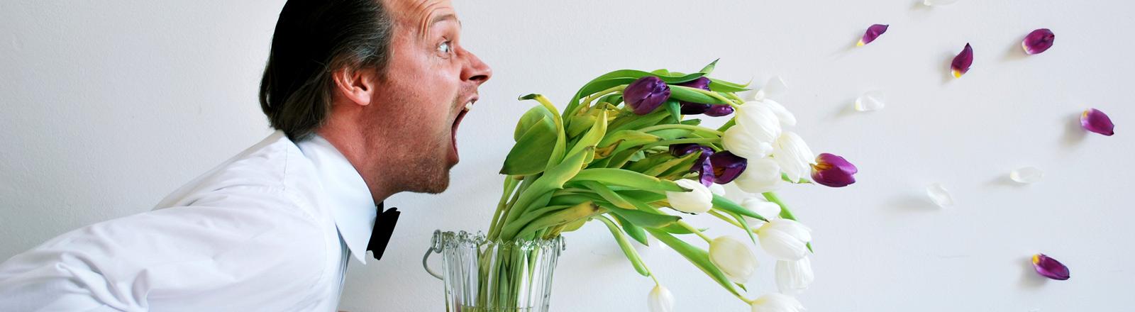Ein Mann schreit einen Strauß Tulpen an.