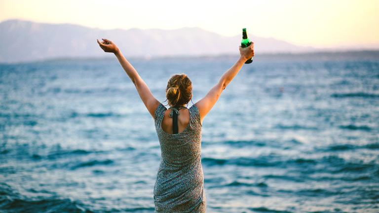 Eine Frau hebt am Strand euphorisch die Arme.