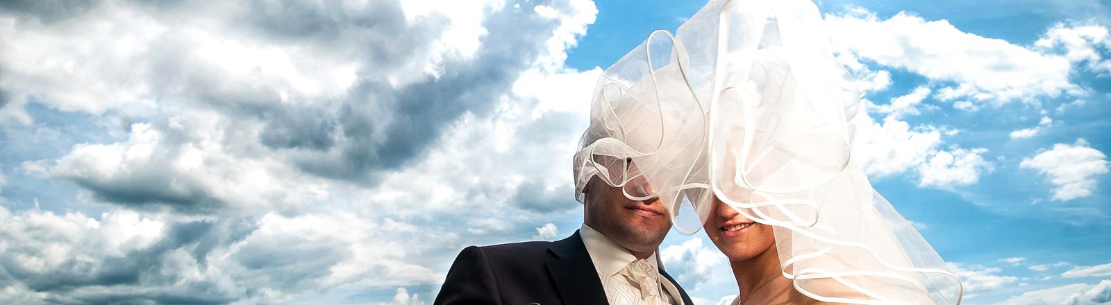 Ein Brautpaar vor Wolkenhimmel mit dem Schleier der Braut im Gesicht.