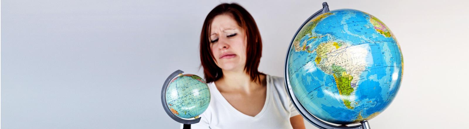 Eine Frau schaut angewidert auf zwei Globen.
