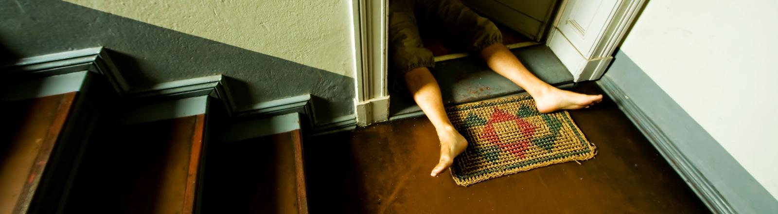 Füße, die aus einer Haustür herausragen.
