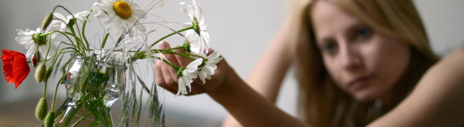 Eine Frau guckt deprimiert auf einen verwelkten Strauß Blumen.