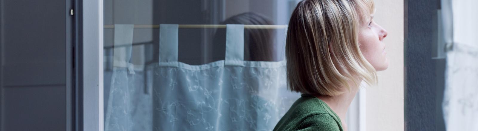 Eine Frau schaut allein, verlassen und sehnsuchtsvoll aus dem Fenster.