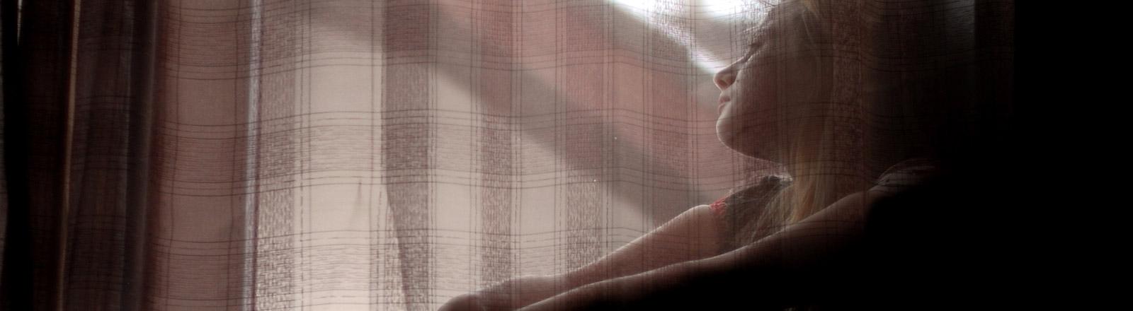 Eine junge Frau sitzt von einem Fenster