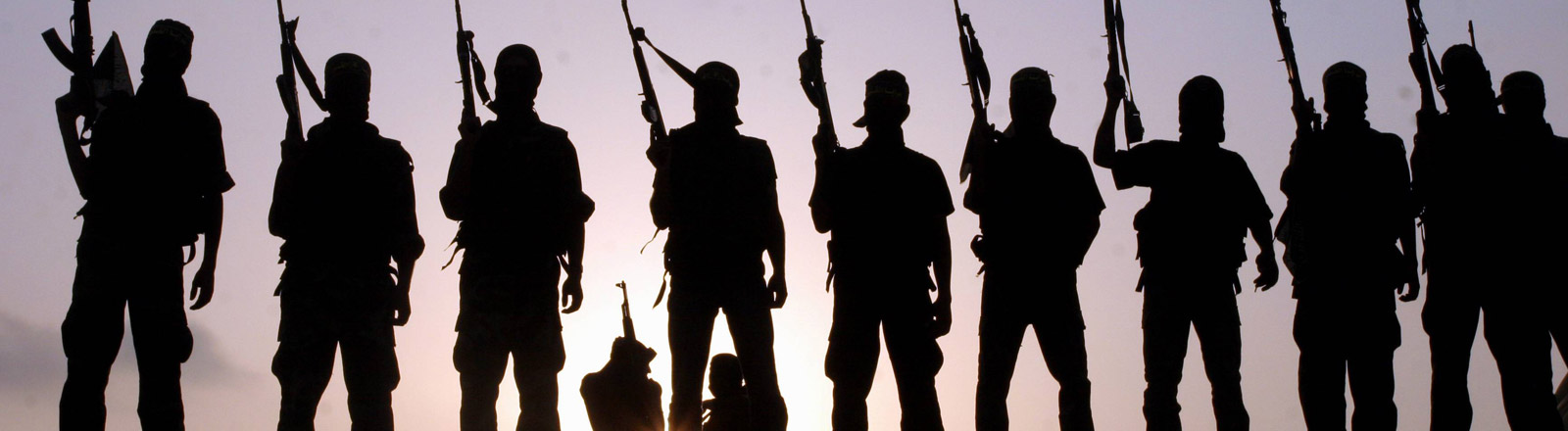 Kämpfer des Islamischen Staates stehen in einer Reihe und halten Waffen nach oben