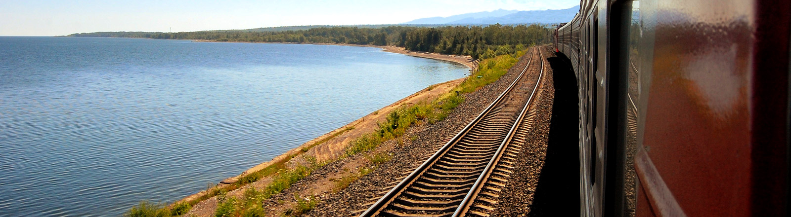 Eine Bahnstrecke an einem See, auf der ein Zug fährt
