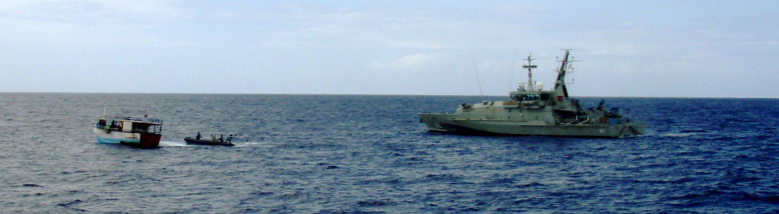 A handout photograph supplied by the Australian Department of Home Affairs on 22 April 2009 showing a boat intercepted by the Border Protection Command off the West Australia coast on 22 April 2009. Australian Navy ship HMAS Wollongong (R) intercepted the vessel approximately 47 nautical miles southwest of Barrow Island and discovered 32 people on board, all Sri Lankan men.