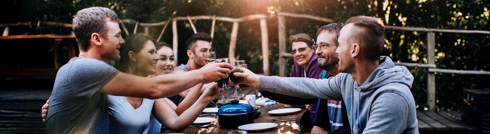 Junge Leute stoßen an einer langen Dinnertafel miteinander an.