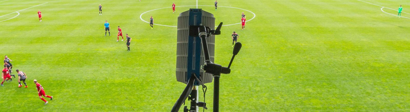 180-Grad-Kamera, Im HIntergrund Fußballfeld mit Spielern