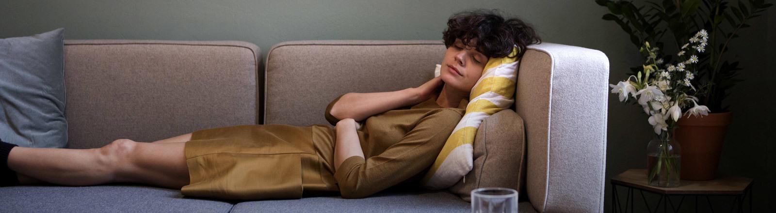 Eine Frau liegt auf einem Sofa