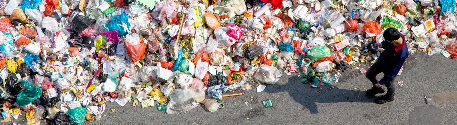Ein Mann neben einem Müllberg in China